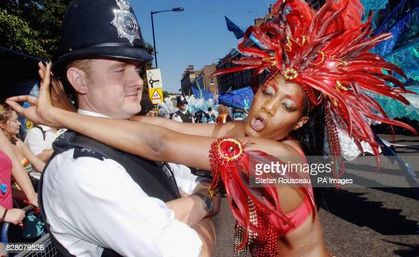 A reveller from Trinidad dances with a reluctant policeman at the Notting Hill Carnival in west London The streets of Notting Hill are packed as...