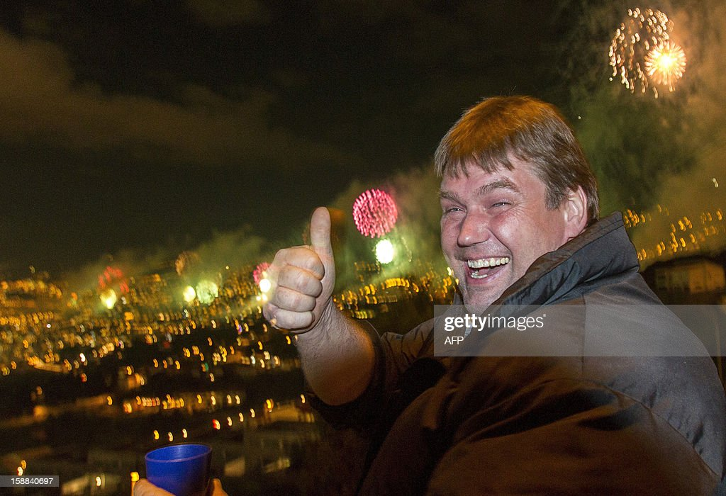A reveller gives a thumbs up as he watches the fireworks above Funchal Bay, Madeira Island, to celebrate the arrival of the New Year on January 1, 2013. World cities from Sydney to Dubai rang in the New Year with a spectacular global wave of firework displays.