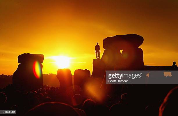 A reveller greets the sun as it rises above Stonehenge on the day of the Summer Solstice June 21 2003 in Wiltshire England More than 30000 people...