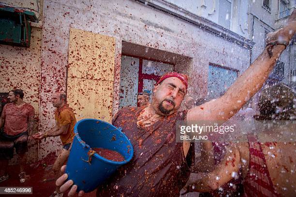 A reveller holds a bucket of tomato pulp during the annual 'tomatina' festivities in the village of Bunol near Valencia on August 26 2015 Some 22000...