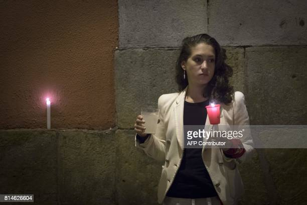 A reveller holds a candle after the singing of 'Pobre de Mi' which marks the end of the San Fermin festival in Pamplona early on July 15 2017 00 am...