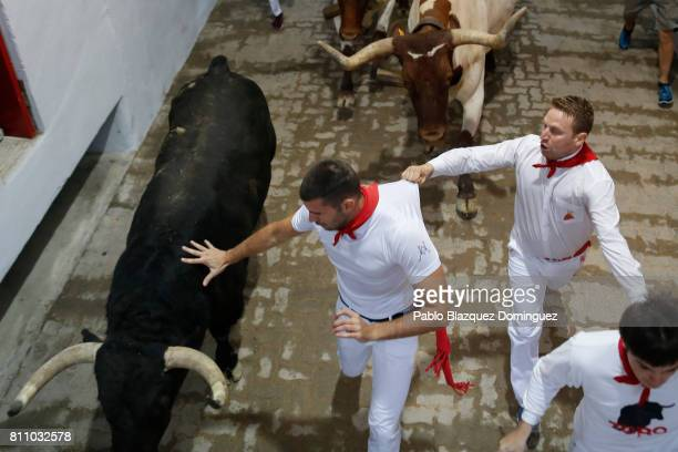 A reveller holds to another runner's tshirt as they run with Puerto de San Lorenzo's fighting bulls entering the bullring during the fourth day of...