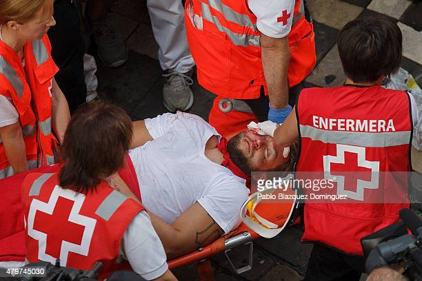 A reveller is assisted by medical staff after running with Jandilla's fighting bulls along the Calle Estafeta during the second day of the San Fermin...