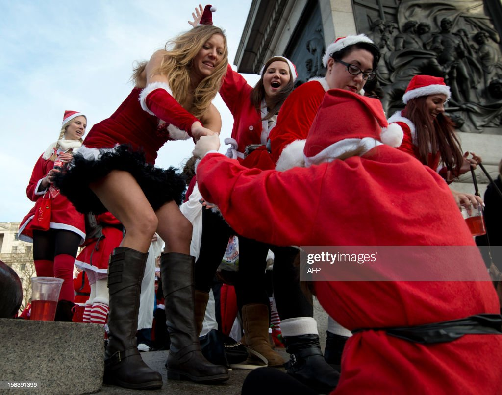 A reveller is helped onto Nelson's Column during a 'Santacon' run through Trafalgar Square in central London on December 15, 2012 less than two weeks before Christmas.