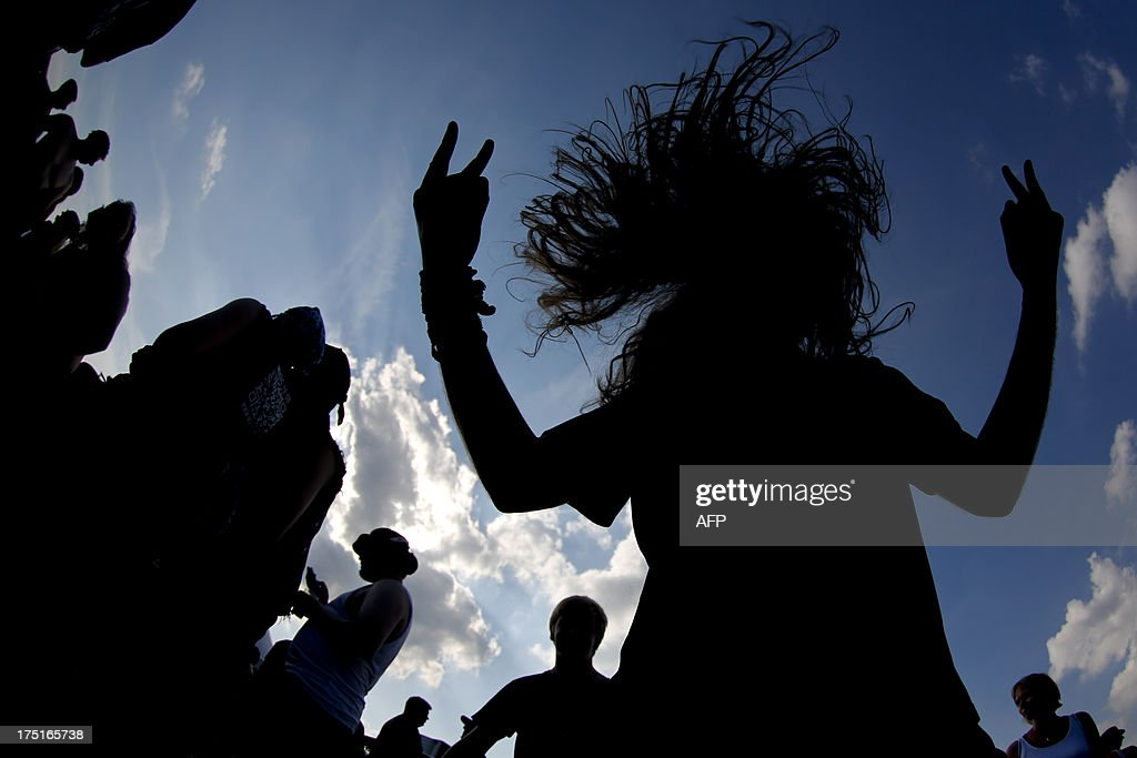 A reveller is silhouetted while headbanging during the 24th heavy metal Wacken Open Air (WOA) Festival 2013 in Wacken, northern Germany on August 1, 2013. With some 80,000 festival visitors it attracts all kinds of metal music fans, such as fans of black metal, death metal, power metal, thrash metal, gothic metal, folk metal and even metalcore, nu metal and hard rock from around the world.