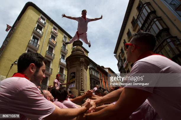 A reveller jumps from a fountain at Navarreria Street as people enjoy the atmosphere during the opening day or 'Chupinazo' of the San Fermin Running...