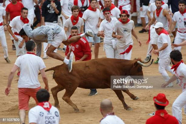 A reveller jumps over a heifer in the bullring during the fourth day of the San Fermin Running of the Bulls festival on July 9 2017 in Pamplona Spain...