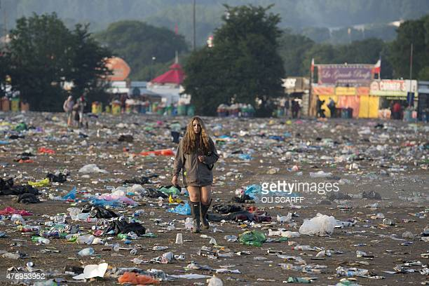 A reveller picks her way through discarded litter as she leaves the Glastonbury Festival of Music and Performing Arts on Worthy Farm near the village...