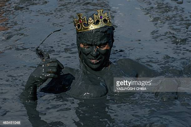 A reveller prepares for 'Bloco da Lama' a mud carnival in Paraty about 250km south of Rio de Janeiro Brazil on February 14 2015 'Bloco da Lama' was...