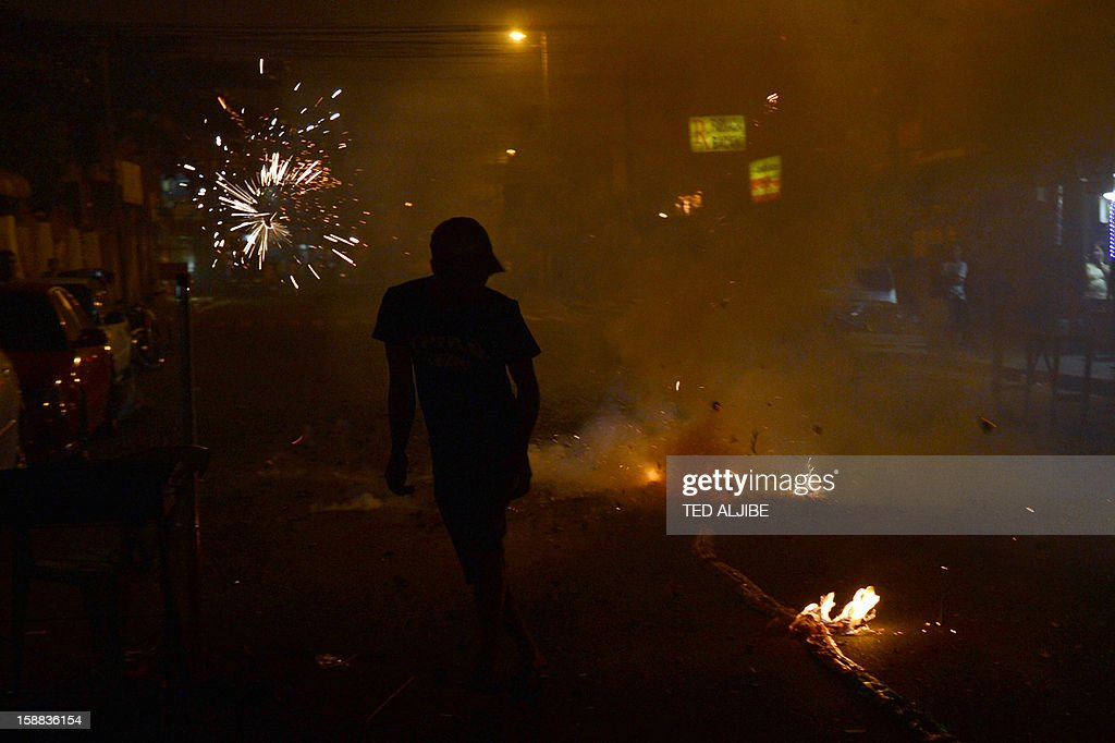 A reveller sets off firecrackers as residents usher New Year in Manila on January 1, 2013. Philippine officials on December 31, reported more injuries from fireworks as the emergency services braced for a night of thunderous and sometimes deadly merrymaking to usher in the new year. AFP PHOTO/TED ALJIBE