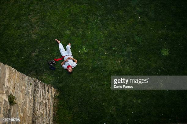 A reveller sleeps on a public park during the opening day or 'Chupinazo' of the San Fermin Running of the Bulls fiesta on July 6 2015 in Pamplona...