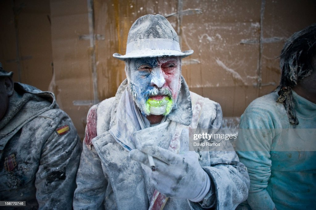 A Reveller smokes during the battle of 'Enfarinats', a flour fight in celebration of the Els Enfarinats festival on December 28, 2012 in Ibi, Spain. Citizens of Ibi annually celebrate the festival with a battle using flour, eggs and firecrackers. The battle takes place between two groups, a group of married men called 'Els Enfarinats' which take the control of the village for one day pronouncing a whole of ridiculous laws and fining the citizens that infringe them and a group called 'La Oposicio' which try to restore order. At the end of the day the money collected from the fines is donated to charitable causes in the village. The festival has been celebrated since 1981 after the town of Ibi recovered the tradition but the origins remain unknown.