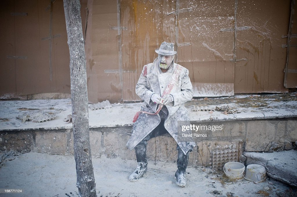 A Reveller smokes during the battle of 'Enfarinats', a flour fight in celebration of the Els Enfarinats festival on December 28, 2012 in Ibi, Spain. Citizens of Ibi annually celebrate the festival with a battle using flour, eggs and firecrackers. The battle takes place between two groups, a group of married men called 'Els Enfarinats' which take the control of the village for one day pronouncing a whole of ridiculous laws and fining the citizens that infringe them and a group called 'La Oposicio' which try to restore order. At the end of the day the money collected from the fines is donated to charitable causes in the village. The festival has been celebrated since 1981 after the town of Ibi recovered the tradition but the origins remain unknown.Ê