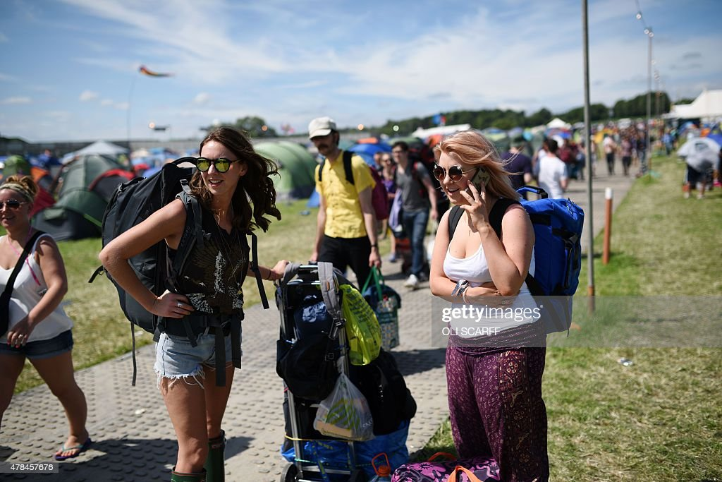 A reveller speaks to her friend on a mobile telephone after arriving at the Glastonbury Festival of Music and Performing Arts on Worthy Farm near the...