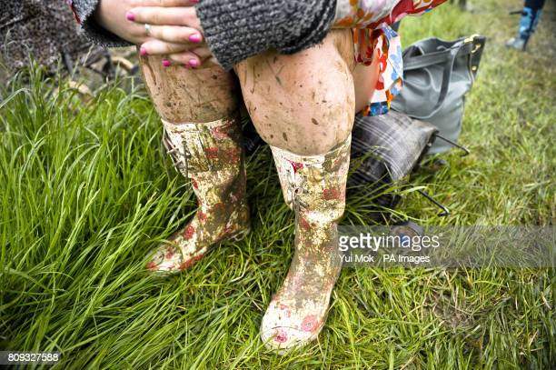 A reveller splattered with mud takes a rest as festival goers arrive at the Glastonbury Festival in Somerset