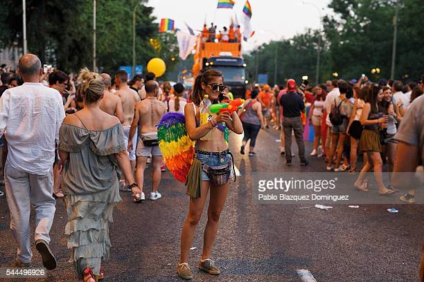A reveller wearing wings with the raimbow colours speaks on the phone as she takes part on the Madrid Gay Pride Parade on July 02 2016 in Madrid...