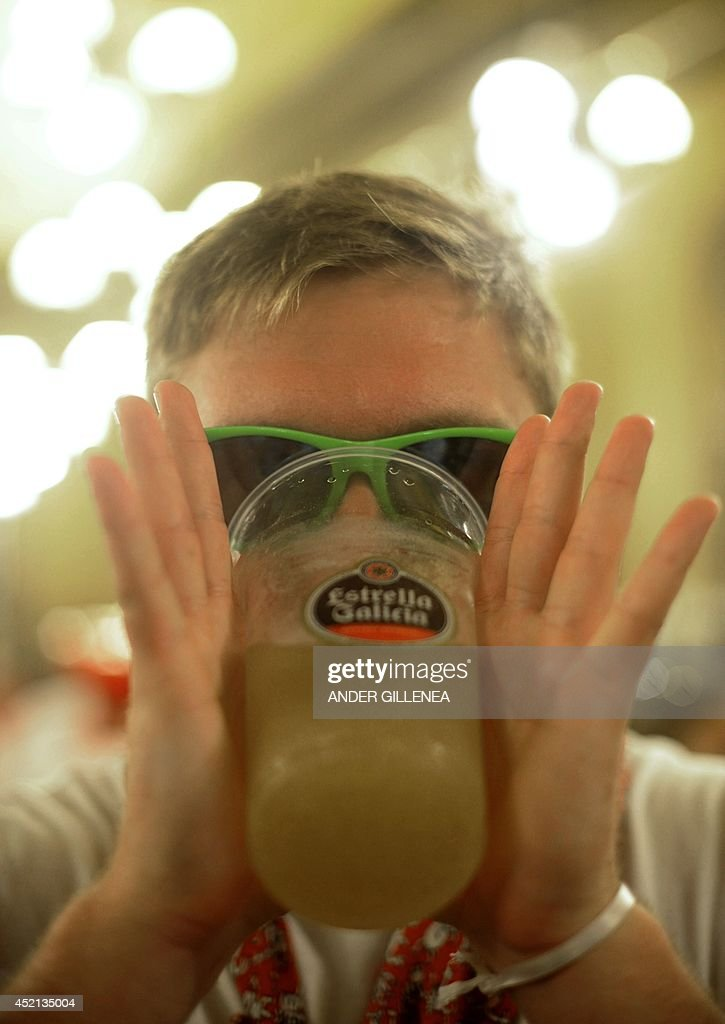 A reveller with green sunglasses drinks alcohol during the San Fermin Festival in Pamplona, northern Spain on July 13, 2014. The Spanish city of Pamplona, famous for its San Fermin festival that mixes bull runs with round-the-clock drinking, has launched a campaign to stop sexual assaults during the week-long fiesta.