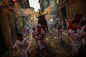 Revellers and children are 'chased' by the 'Toro de Fuego' as it runs throught the streets during the opening day of the San Fermin Running of the...