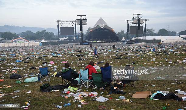 Revellers are pictured in front of the Pyramid Stage surrounded by discarded litter at the Glastonbury Festival of Music and Performing Arts on...