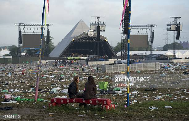 Revellers are pictured in front of the Pyramid Stage surrounded by discarded litter at the end of the Glastonbury Festival of Music and Performing...