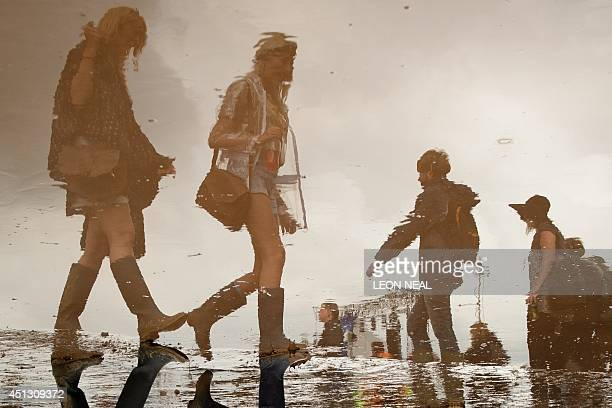 Revellers are reflected in a puddle near to the Pyramid Stage on the first official day of the Glastonbury Festival of Music and Performing Arts on...