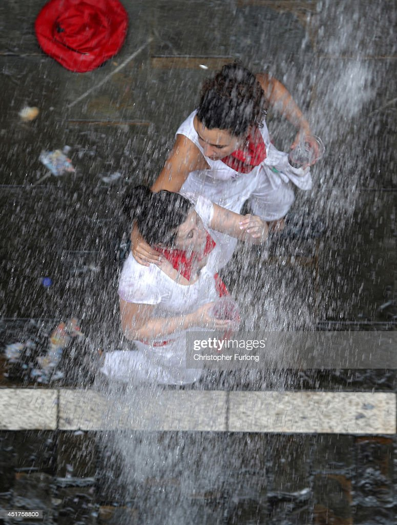 Revellers are soaked in water and wine thrown from balconies during the opening day or 'Chupinazo', of the San Fermin Running of the Bulls fiesta on July 6, 2014 in Pamplona, Spain. The annual Fiesta de San Fermin, made famous by the 1926 novel of US writer Ernest Hemmingway entitled 'The Sun Also Rises', involves the daily running of the bulls through the historic heart of Pamplona to the bull ring.