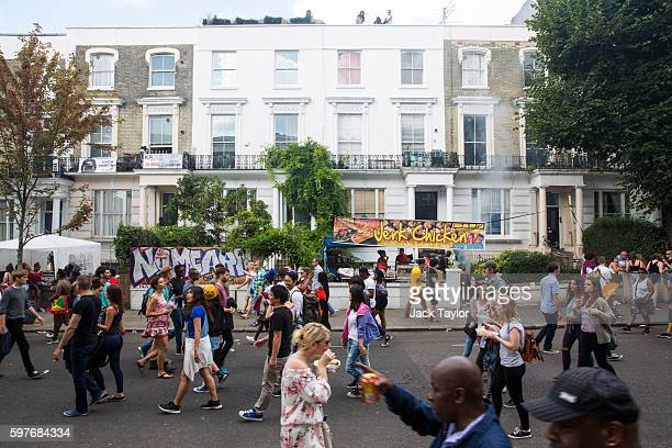 Revellers at Notting Hill Carnival walk through a residential street past a jerk chicken stall on August 29 2016 in London England The Notting Hill...