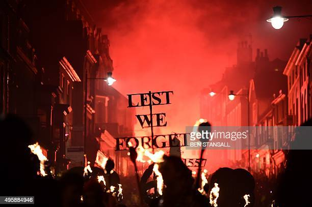 Revellers carry a sign reading 'Lest We Forget' as they parade through the streets of Lewes in Sussex southern England on November 5 during the...