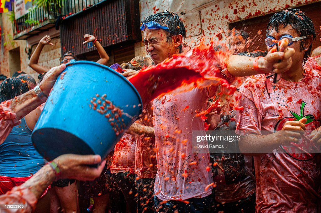 Revellers celebrate covered by tomato pulp while participating the annual Tomatina festival on August 28, 2013 in Bunol, Spain. An estimated 20,000 people threw 130 tons of ripe tomatoes in the world's biggest tomato fight held annually in this Spanish Mediterranean town.