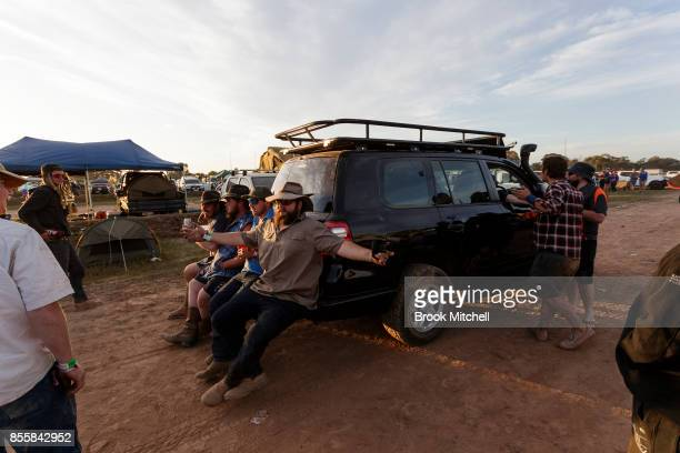 Revellers cling to the back of a police car at the 2017 Deni Ute Muster on September 30 2017 in Deniliquin Australia The annual Deniliquin Ute Muster...