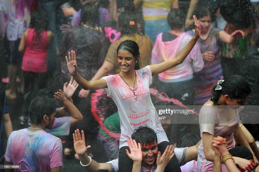 Revellers covered in coloured powders and water celebrate 'Holi' in Hong Kong on March 31, 2013. Holi, the festival of colours where people smear each other with coloured powder and water, is celebrated by Hindus across the world. AFP PHOTO / ANTHONY WALLACE