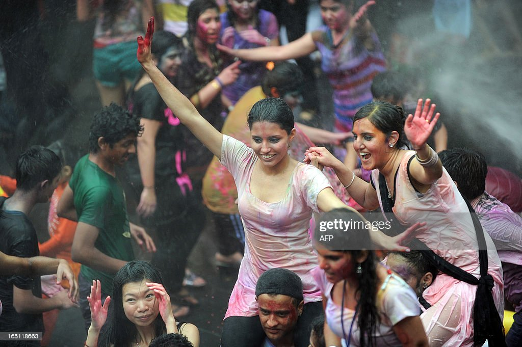 Revellers covered in coloured powders celebrate 'Holi' in Hong Kong on March 31, 2013. Holi, the festival of colours where people smear each other with coloured powder and water, is celebrated by Hindus across the world. AFP PHOTO / ANTHONY WALLACE