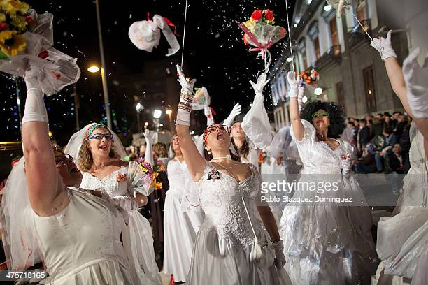 Revellers dressed as brides throw bouquets during the opening parade of the carnival on February 28 2014 in Santa Cruz de Tenerife on the Canary...