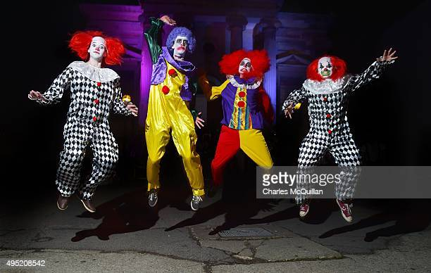 Revellers dressed as clowns pose for photographs as they arrive for a Gothic Ball taking place inside a former church on October 31 2015 in...