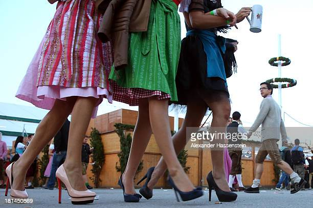 Revellers dressed in traditional Bavarian clothing `Dirndl` walk over the Theresienwiese during day 1 of the Oktoberfest 2013 beer festival at...