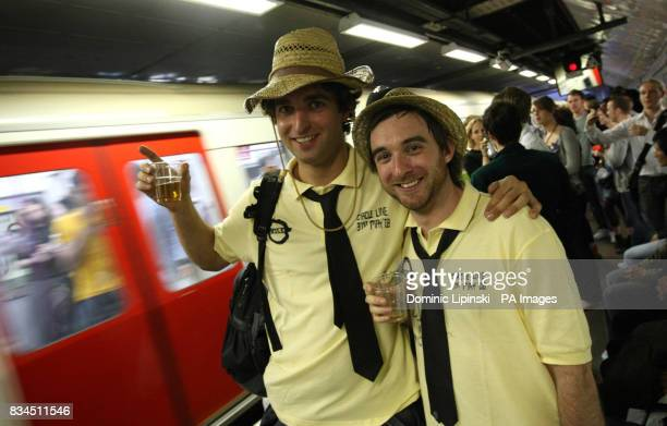 Revellers drink on a Circle line tube platform before the ban on drinking alcohol comes into force at midnight