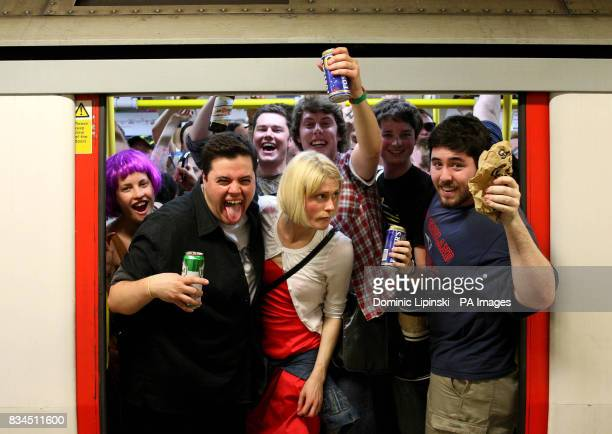 Revellers drink on a Circle line tube train before the ban on drinking alcohol comes into force at midnight