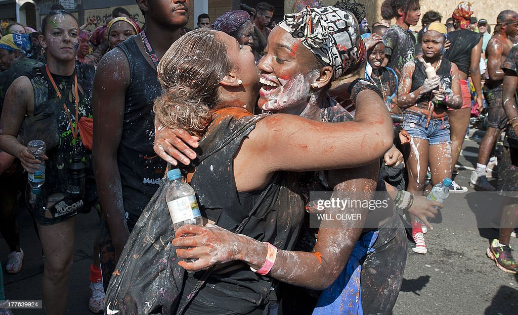 Revellers embrace on the first day of the Notting Hill Carnival in west London on August 25, 2013. Running over two days, the Caribbean carnival puts on a Kid's day on the Sunday when costume prizes are awarded and a 'main parade' day on the Monday.