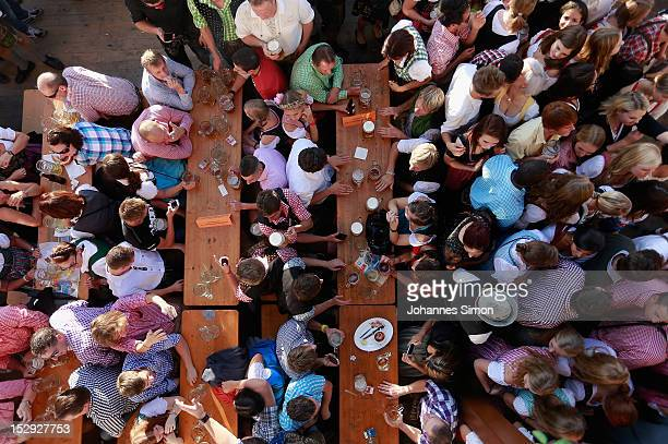 Revellers enjoy themselves as they drink beer outside the Braeurosl beer tent during day 7 of Oktoberfest beer festival on September 28 2012 in...