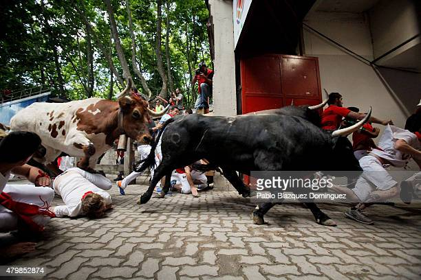 Revellers fall while running with the Tajo and the Reina's fighting bulls entering the bullring during the third day of the San Fermin Running Of The...
