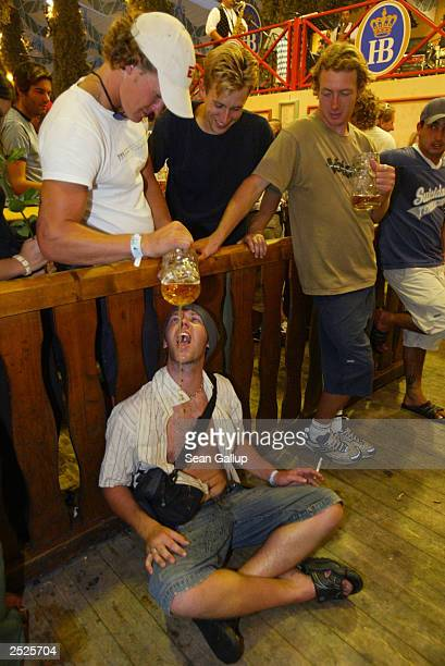 Revellers from Australia douse a friend with beer in the Hofbraeuhaus tent at the annual Oktoberfest celebration September 22 2003 in Munich Germany...