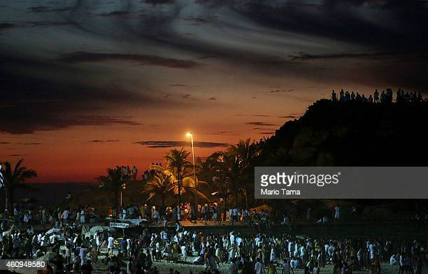 Revellers gather and await the first sunrise of 2015 during New Year's festivities at Arpoador on January 1 2015 in Rio de Janeiro Brazil Up to 2...
