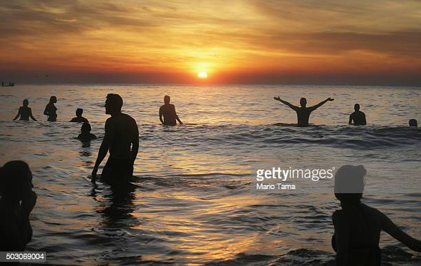 Revellers gather in the Atlantic Ocean near Arpoador during the first sunrise of 2016 on January 1 2016 in Rio de Janeiro Brazil Thousands gather at...
