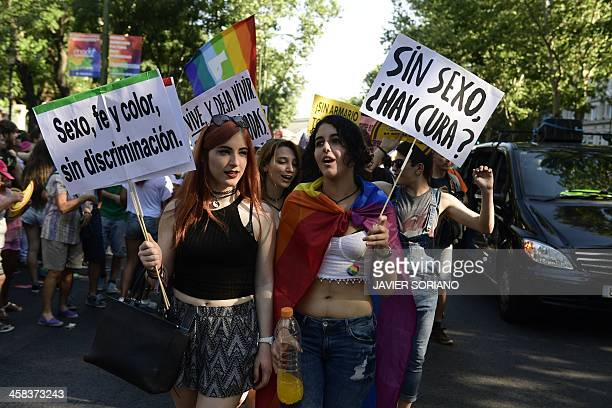 Revellers hold placards in favour of sexual freedoms as they take part in the Gay Pride Parade in Madrid on July 2 2016 / AFP / JAVIER SORIANO