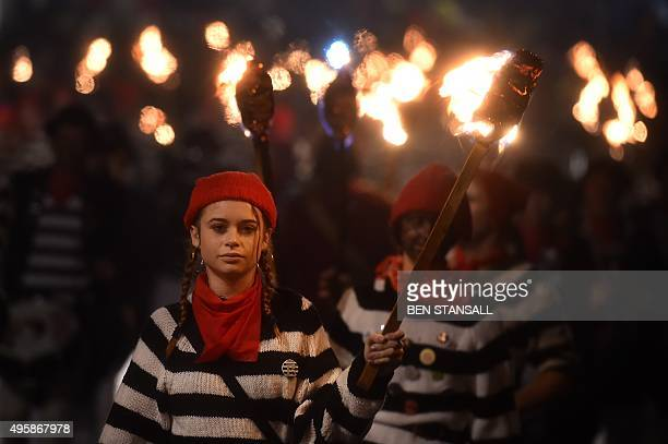 Revellers hold torches as they parade through the streets of Lewes in Sussex southern England on November 5 during the traditional Bonfire Night...