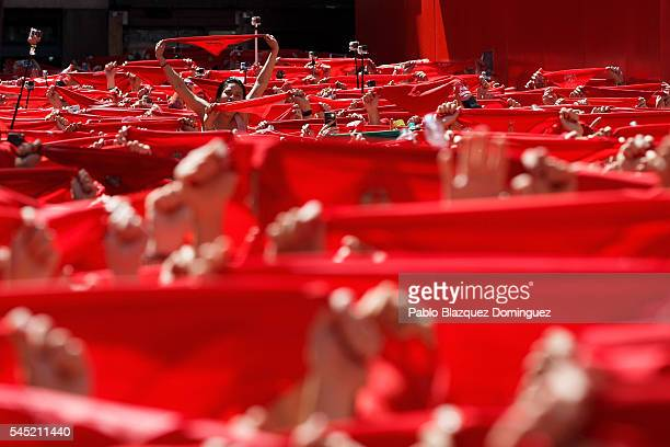 Revellers hold up their red handkerchiefs during the opening day or 'Chupinazo' of the San Fermin Running of the Bulls fiesta on August 6 2016 in...