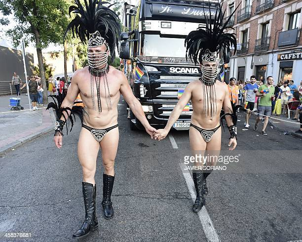Revellers in fancy dress hold hands during the Gay Pride Parade in Madrid on July 2 2016 / AFP / JAVIER SORIANO