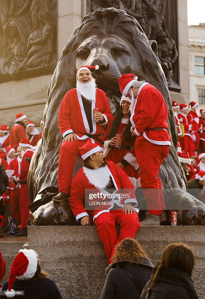 Revellers in Santa costumes gather around Nelson's Column during a 'Santacon' in Trafalgar Square in central London on December 15, 2012, less than two weeks before Christmas. AFP PHOTO / LEON NEAL