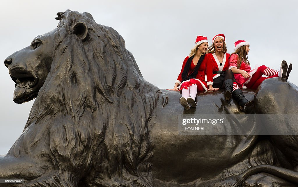 Revellers in Santa costumes sit on a lion statue at the base of Nelson's Column during a 'Santacon' in Trafalgar Square in central London on December 15, 2012, less than two weeks before Christmas.