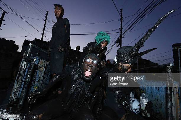 Revellers in the 3canal Jouvay band 'Blk Jab Nation' parade wearing black paint during j'ouvert as part of Trinidad and Tobago Carnival on February...